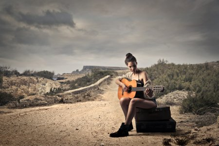 Photo for Girl playing guitar on a dusty road - Royalty Free Image