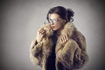 Elegant girl wearing sunglasses and a fur coat