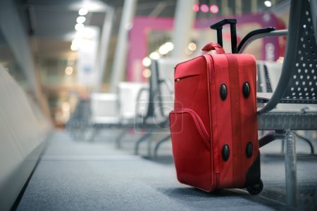 Travel red suitcase in airport unowned...