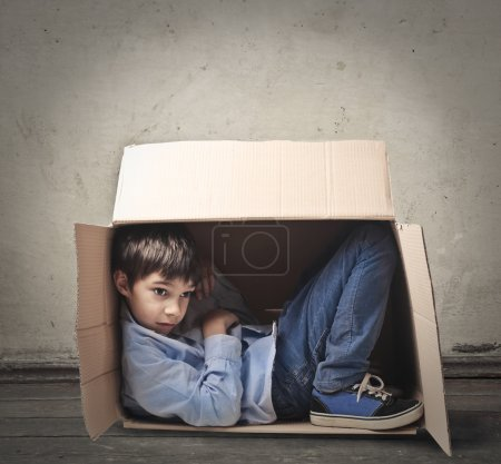 Photo for Child tried to get into a cardboard box - Royalty Free Image