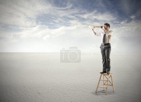Photo pour Un homme regardant grimpé une échelle à travers un périscope - image libre de droit