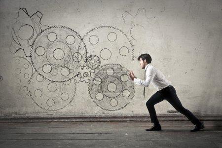 Photo pour Homme poussant des engrenages illustrations dans un mur - image libre de droit