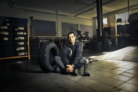 Photo pour Mécanicien assis sur le plancher de l'atelier - image libre de droit