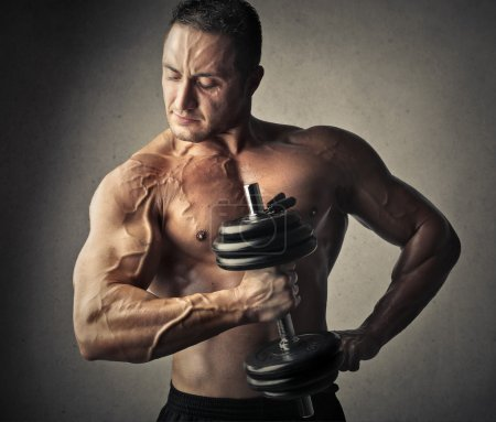 Photo for Strong man looking as your muscles working with dumbbell - Royalty Free Image