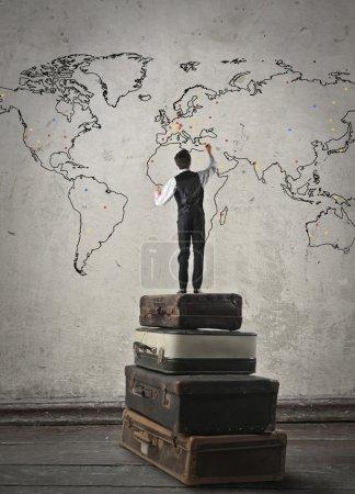 Photo pour L'homme a escaladé une grande valise plaçant des points sur différents pays du monde - image libre de droit