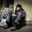 Homeless man sitting on the floor next to garbage ...