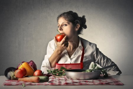 Photo for Woman on table eating vegetables without cooking - Royalty Free Image