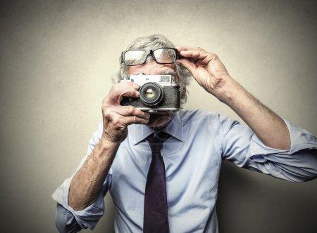 Photo pour Homme d'affaires prenant des photos avec un vieil appareil photo - image libre de droit