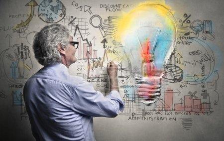 Photo pour Homme peignant une murale avec une ampoule - image libre de droit