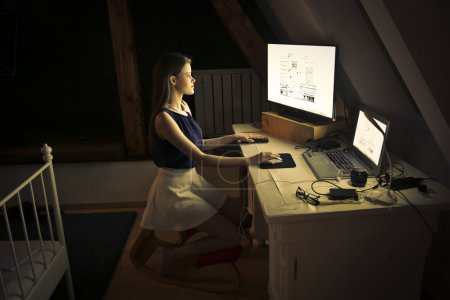 Photo for Young girl working on computer at night - Royalty Free Image