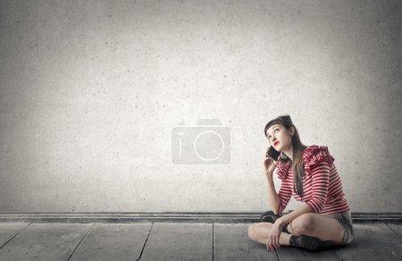Foto de Mujer hablando por teléfono, sentada en el suelo - Imagen libre de derechos