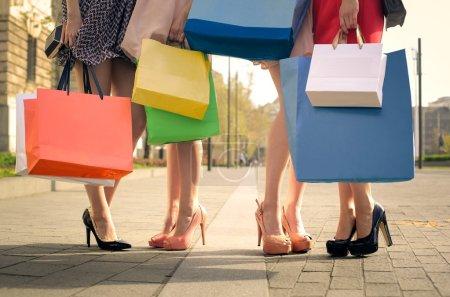 Photo pour Quatre filles tenant des sacs à provisions - image libre de droit