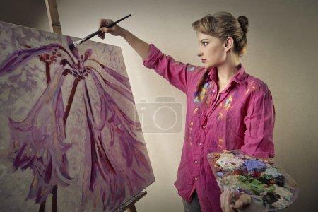 Photo pour Une femme peignant des fleurs sur une toile - image libre de droit
