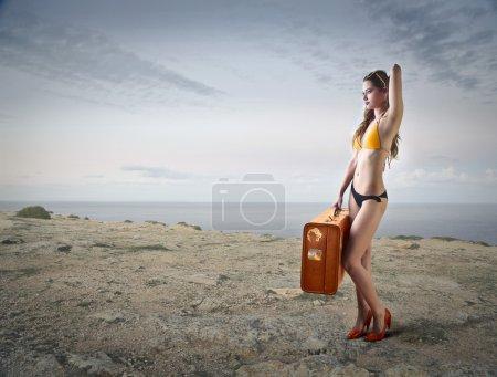 Photo pour Une jeune femme portant une valise à la plage - image libre de droit
