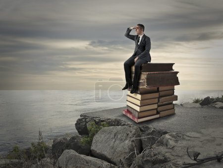 Photo for Businessman sitting on a pile of books - Royalty Free Image