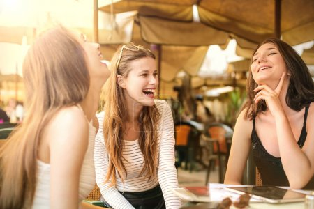 Women laughing at a cafe