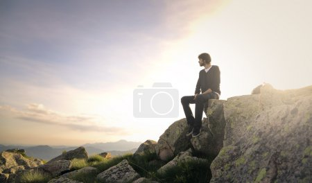 Man sitting on a rock looking far away