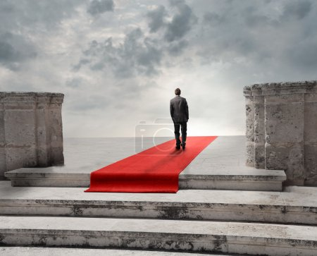 Man walking on a red carpet towards a cloudy sky