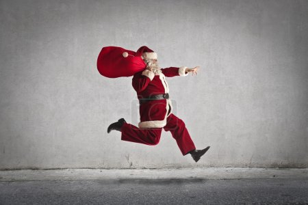Photo for Santa Claus running while carrying a big red bag - Royalty Free Image