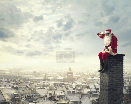 Photo for Santa Claus admiring the horizon from the chimney of a house - Royalty Free Image