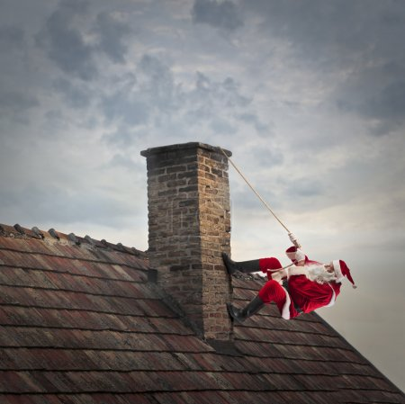 Photo for Santa Claus climbing on a chimney to enter a house - Royalty Free Image