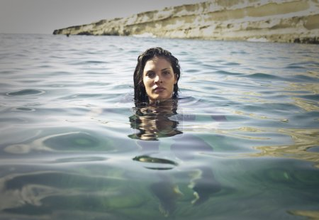 Photo for Young woman floating in the water at the seaside - Royalty Free Image