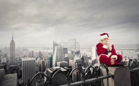 Photo for Santa Claus doing a phone cal while sitting outdoors in an american city - Royalty Free Image
