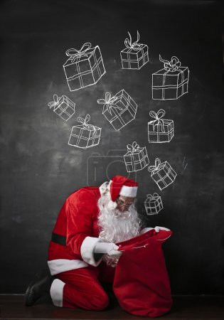 Foto de Santa está buscando en su bolso los regalos. - Imagen libre de derechos