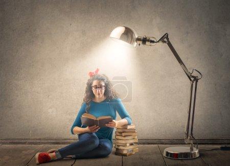 Photo pour Une femme semble si diligente à lire tous ces livres - image libre de droit