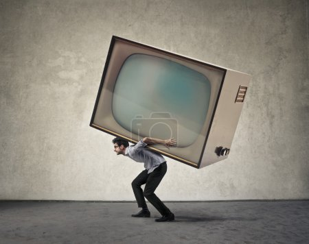 Photo for Man carrying a giant tv set - Royalty Free Image