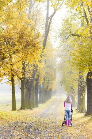 Photo pour Femme avec une poussette sur pas dans la ruelle automnale - image libre de droit