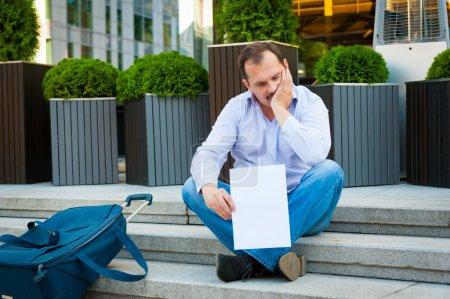 Sad businessman sitting on the steps