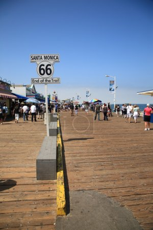 Foto de SANTA MONICA, CALIFORNIA - JULY 1: Route 66 sign on the pier on July 1, 2012 in Santa Monica, California. Old 66 was over 2,000 miles long from Chicago to Los Angeles and was decommissioned in 1984. - Imagen libre de derechos