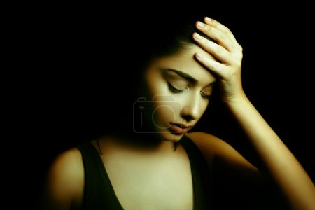 Depression. Sad Young Woman with Face in the Dark
