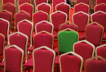 Photo pour Diversité, concept différent ou unique - chaise verte dans un groupe de chaises rouges - image libre de droit