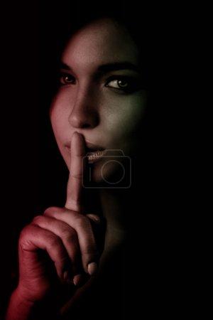 Shhh secret concept - woman with finger over lips...