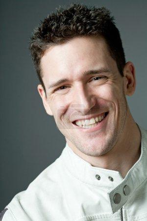 Photo pour Joyeux jeune homme beau en veste en cuir blanc . - image libre de droit