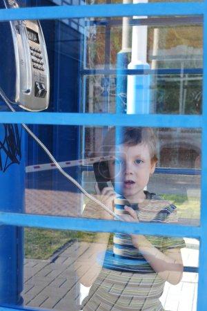 Photo pour Mignon petit enfant s'exprimant par téléphone rue - image libre de droit