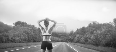 Woman jogger looking down empty stretch of road
