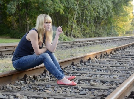 Photo for Frustrated young woman with cigarette sitting on rail track - Royalty Free Image