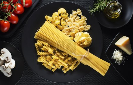 Photo for Raw mixed pasta on black background overhead shoot - Royalty Free Image