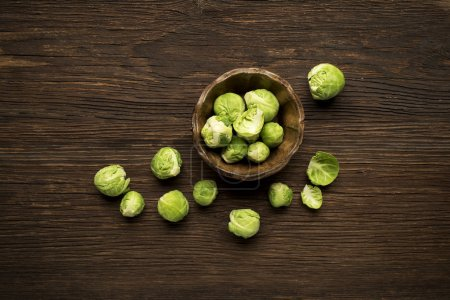 Photo for Bunch of fresh Brussels sprouts in a cup on wooden background. - Royalty Free Image