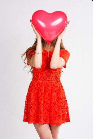 Woman holding red heart balloon