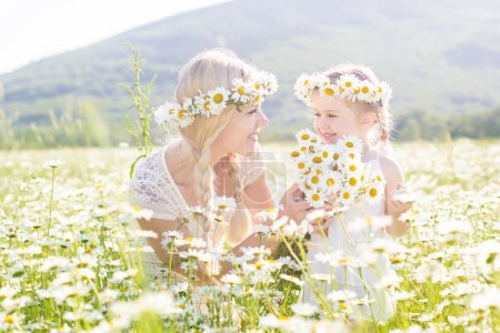 Family mother and child in field of daisy flowers