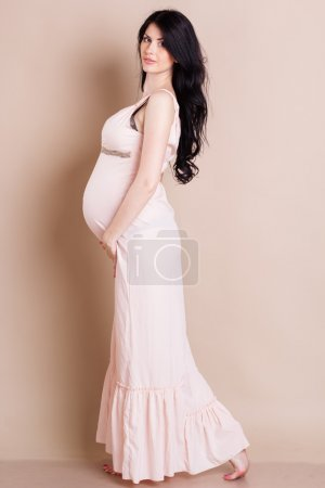 Studio portrait of beautiful pregnant woman holding her belly
