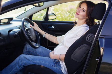Pregnant pretty young woman is sitting in black car
