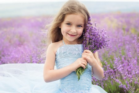 Happy little girl in lavender field with bouquet