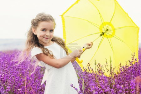 Little princess girl in lavender field with yellow umbrella