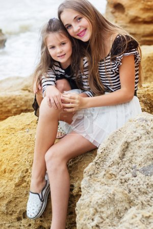 Two little sister girls playing on the beach