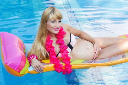 Pregnant blonde woman is lying on mattress in swimming pool